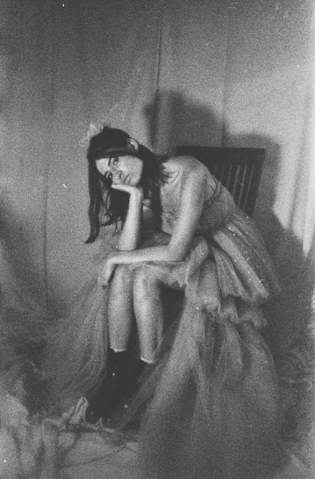 Woman sitting slouched on a chair in a poofy tulle dress. Taken from the shoot - I Didn't Go to Prom.